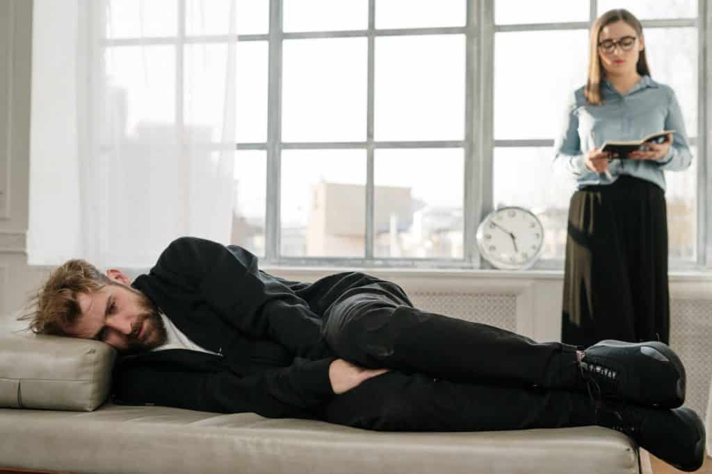 Man in black jacket lying on bed