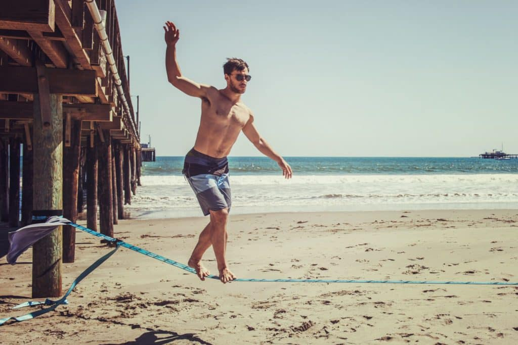 man wearing sunglasses and board shorts standing on rope