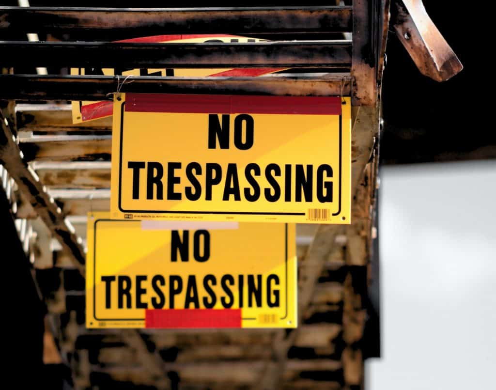 NO TRESPASSING signs hanging from a fire escape on a downtown building.