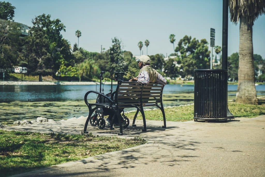 Old retired men is sitting on the park bench at Echo Park in Los Angeles