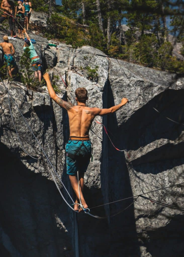 Slackline suspendend from rock face while a shirtless man balances on it