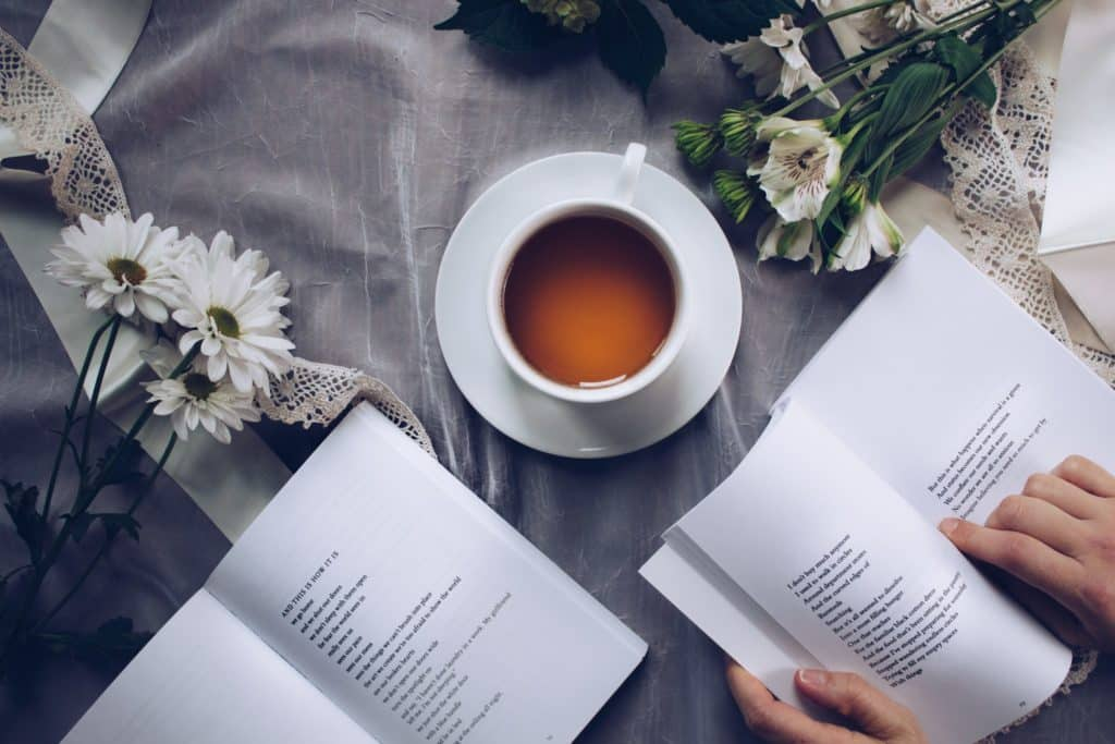 Woman reading a book with tea and flowers.