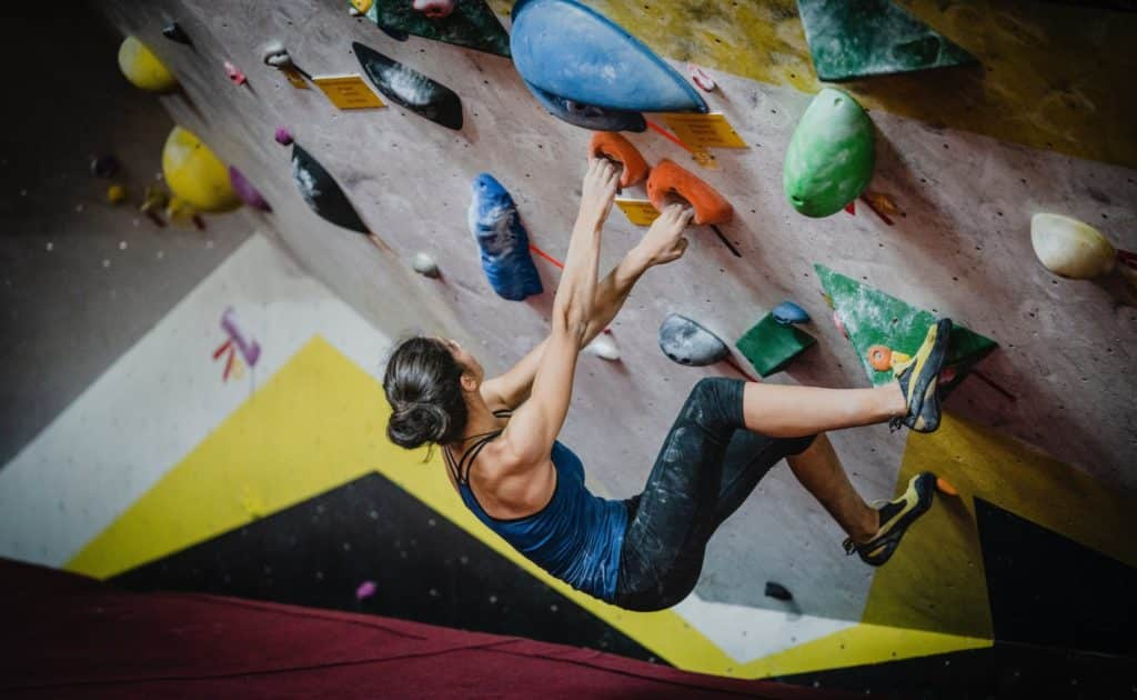 woman rock climbing inside building