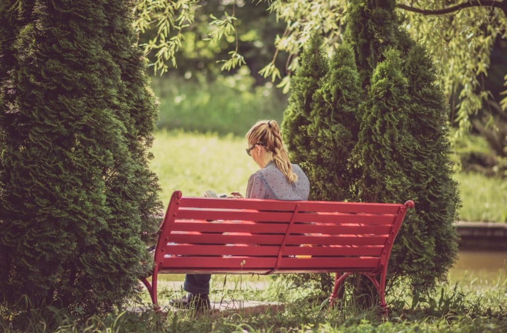 woman sitting on red wooden bench